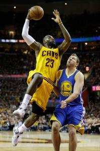 LeBron James takes David Lee to the basket (Photo courtesy of Tony Dejak)